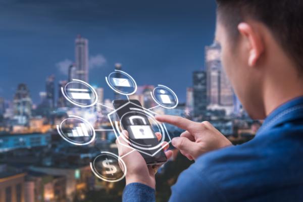 大都市にてセキュリティ機能があるスマートフォンを操作する男性
